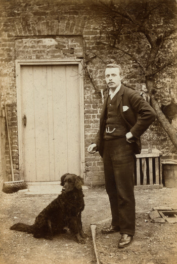 J H Wilson with his dog behind the shop at Weaverthorpe - about 1897