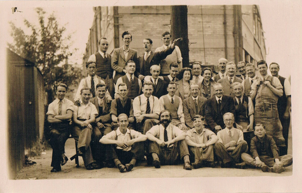 Luigi (Arthur) is 2nd from the right of the people seated on the chairs